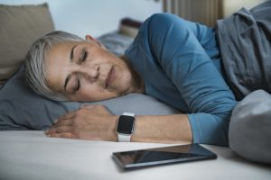 Sleep Apps - Tech-savvy Senior Woman Sleeping in Bed