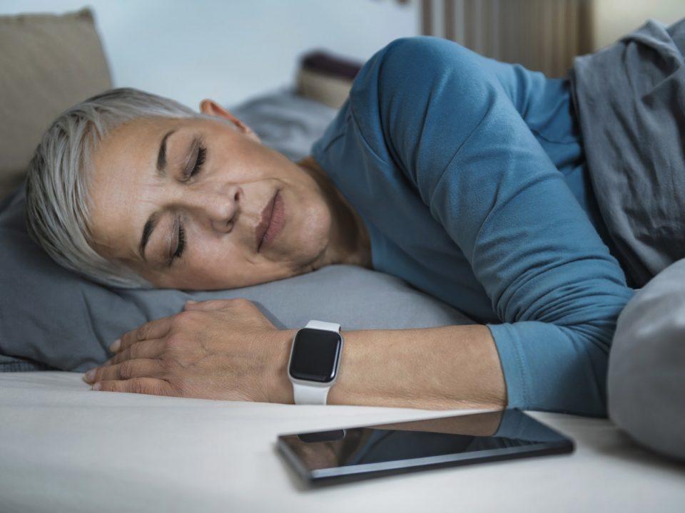 Sleep Apps - Tech-savvy Senior Woman Sleeping in Bed